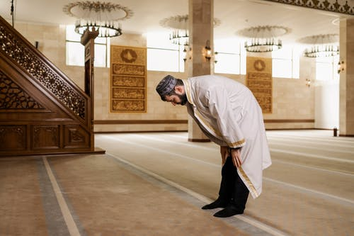 Man in White Thobe Bowing Down
