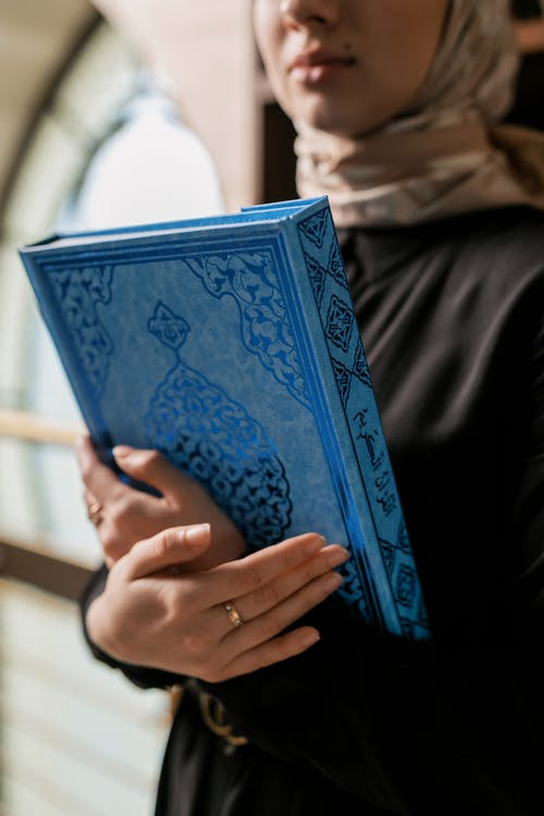 Woman Holding a Book with Blue Cover