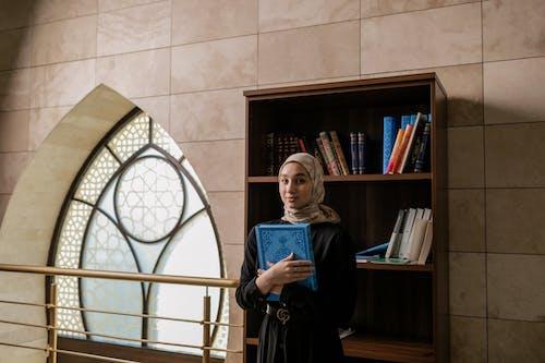 Woman in Black Dress Holding Blue Book Standing Near Brown Wooden Book Shelf