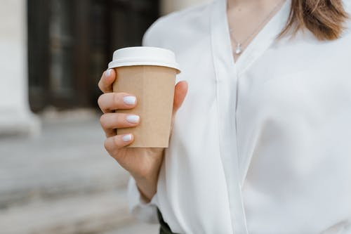 Woman Wearing White Blouse Holding a Paper Cup