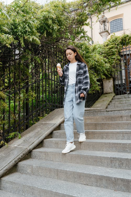 Woman Wearing Long Sleeves and Denim Pants Going Down the Concrete Stairs While Holding Ice Cream Cone