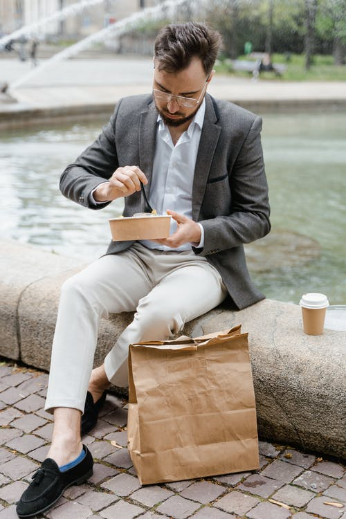 Man Wearing Gray Jacket Sitting by the Water Pond Eating Takeaway Meal