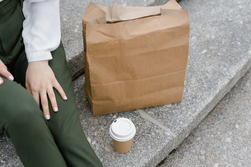 Person in Green Pants Holding Brown Paper Bag