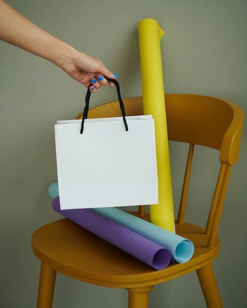 Foto profissional grátis de cadeira de madeira, fundo verde, holding