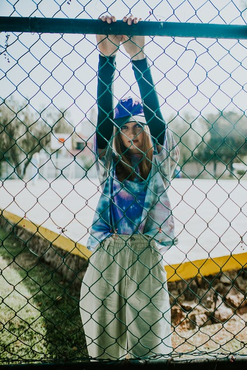 Woman Hanging on to the Wire Mesh Fence Wearing Sports Attire