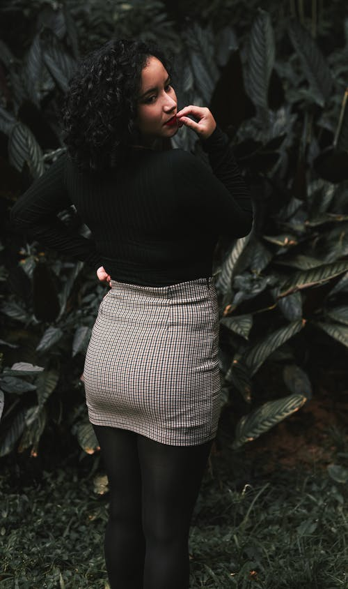 Woman in Black Long Sleeve and White Skirt Standing Near Green Plants
