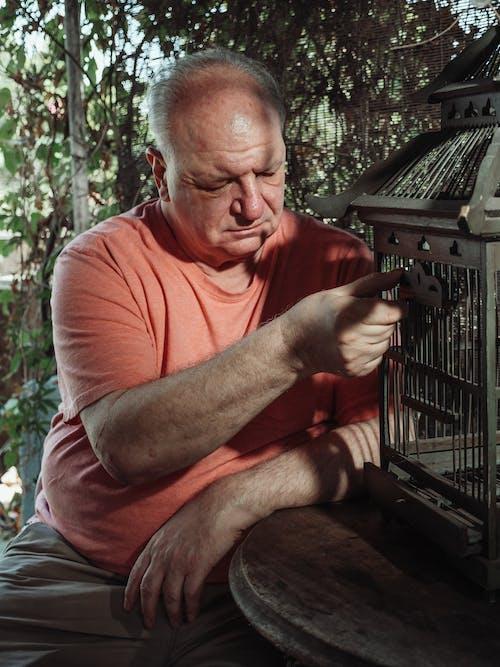 An Elderly Man Holding a Door of a Birdcage