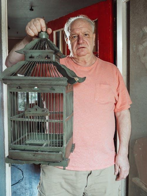 An Elderly Man Carrying a Birdcage