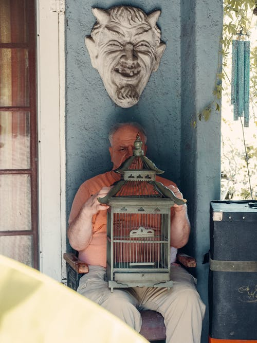 An Elderly Man with a Birdcage on His Laps
