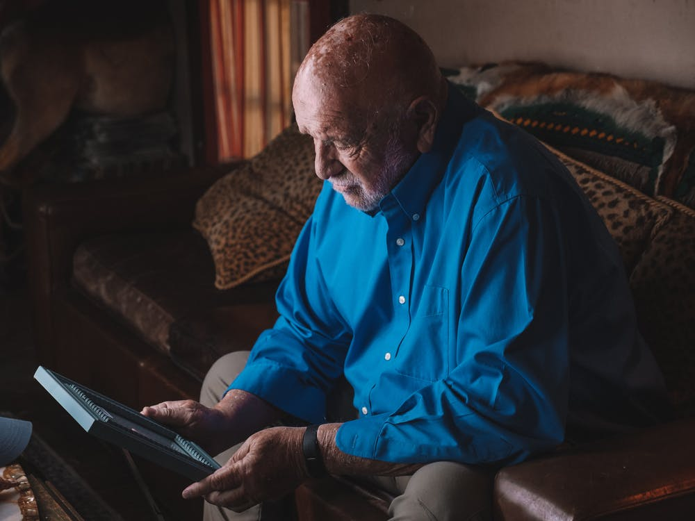 Man Sitting on a Sofa Holding a Photo Frame