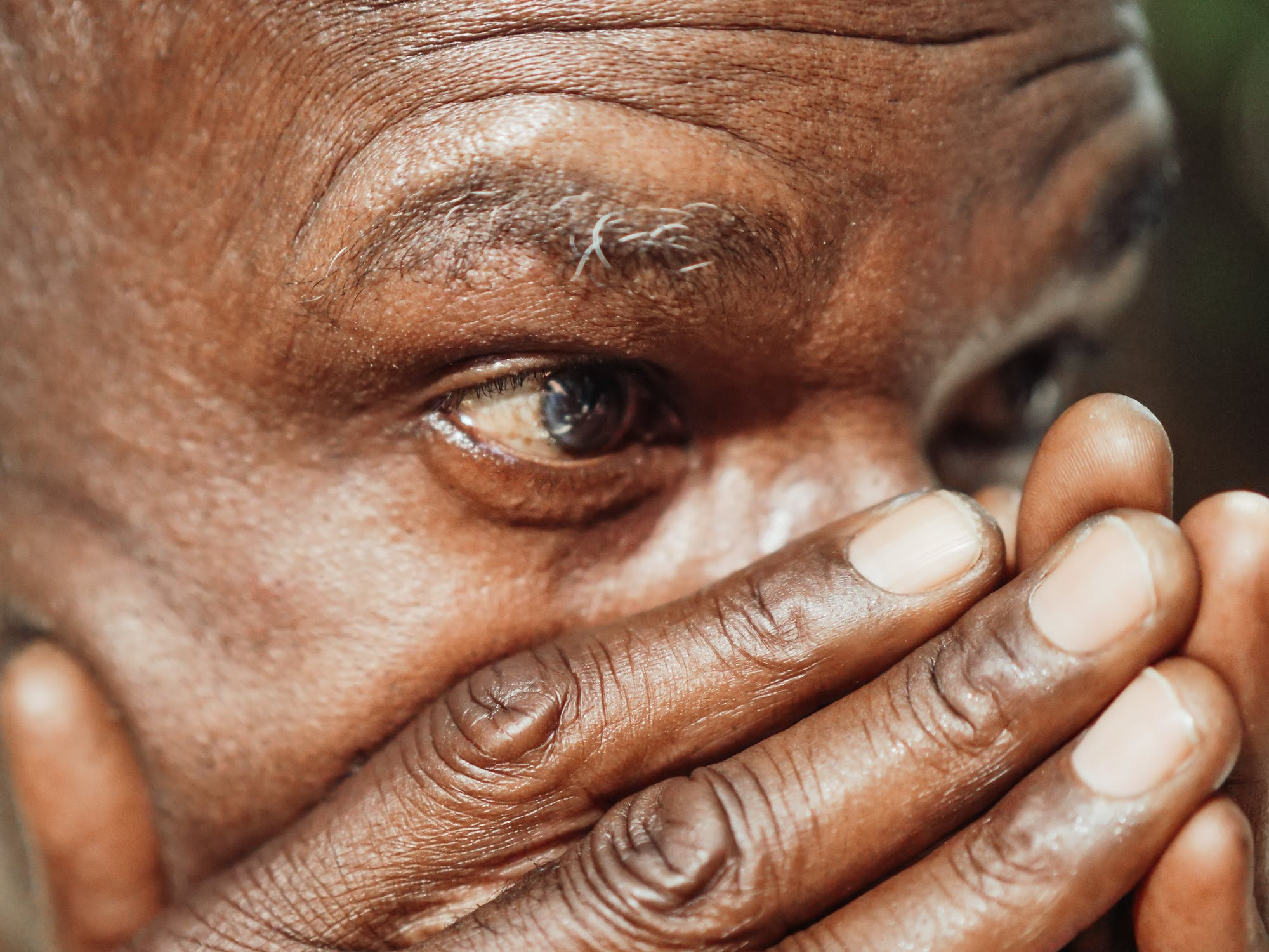 A close up on a man's eyes as he covers is nose and mouth with his hands. Photo used courtesy of Pexels.com.