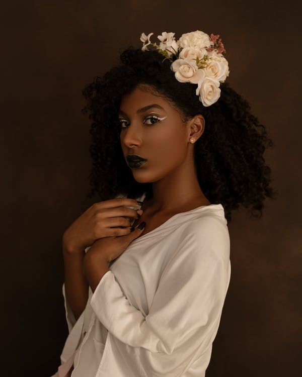 Woman in White Shirt With White Flower on Ear