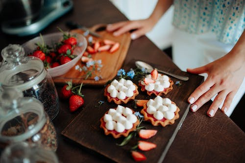 Crop woman with cookies and strawberries