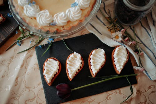 Top view of delicious homemade desserts decorated with cream placed on table near cake and flowers in kitchen