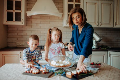 Children and lady in casual clothes standing near table with tasty desserts with cream and strawberry in light kitchen with cupboards