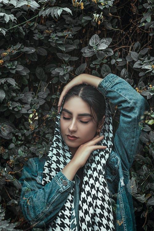 Woman in Blue Denim Jeans Lying on Green Leaves