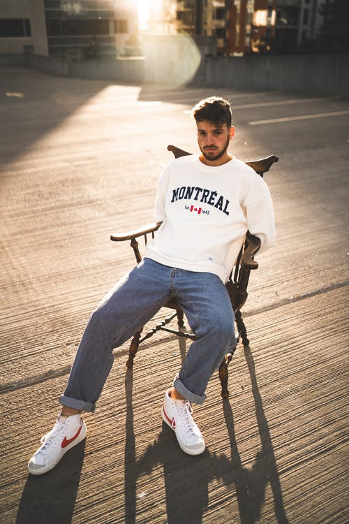 Man in White and Black Crew Neck Shirt and Blue Denim Jeans Sitting on Black Metal