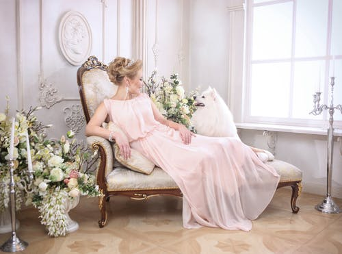Woman in Pink Dress Sitting on Brown Wooden Armchair
