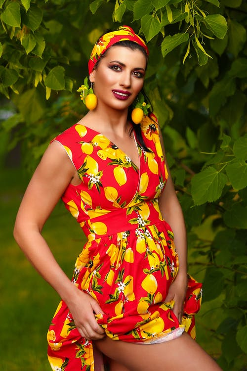 Woman in Yellow and Red Floral Dress Standing Beside Green Plant