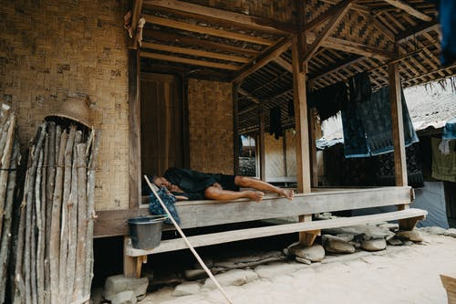 Man in Black T-shirt and Blue Denim Jeans Lying on Brown Wooden Bed