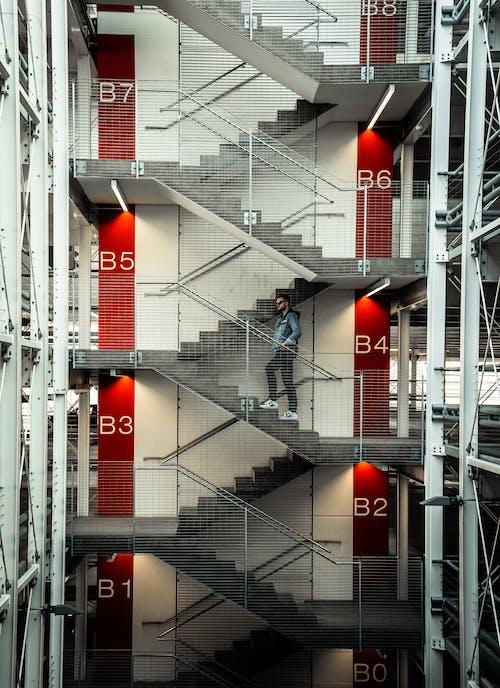 Man in Black Jacket and Pants Walking on Black Staircase
