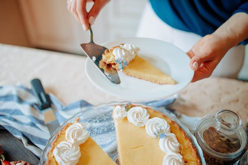 Anonymous woman with pie on plate near table in kitchen