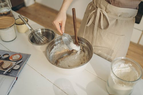 A Person Pouring Flour into the Bowl Using a Measuring Spoon