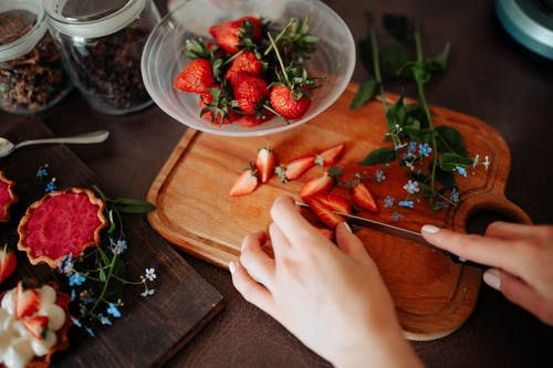 A Person Slicing Red Strawberries