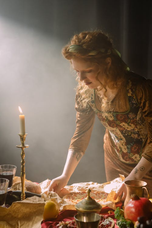 A Woman in Floral Dress Holding a Pizza on the Table Near the Candle