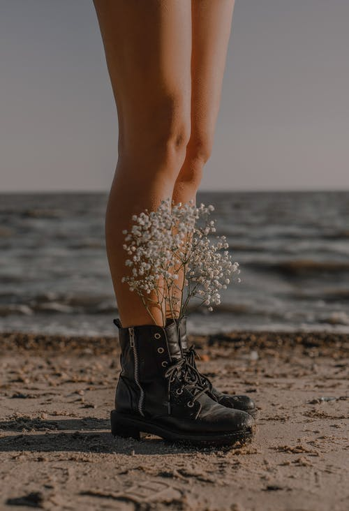 Woman in Black Lace Up Boots Standing on Beach Shore