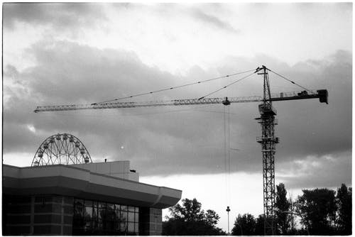 Grayscale Photo of a Crane Over the Building