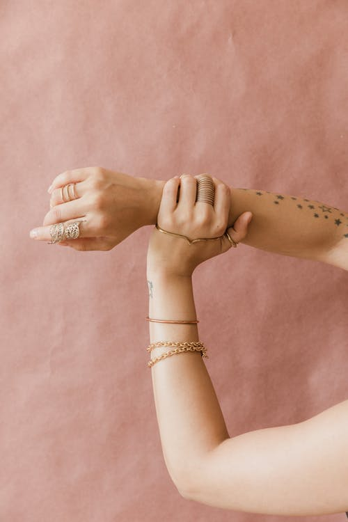Person's Arms Wearing Gold Bracelet