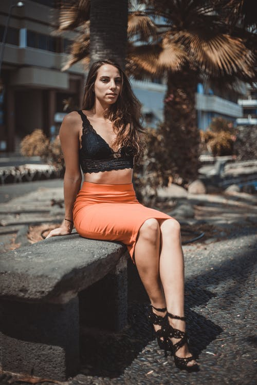 Woman in Black and Orange Lingerie Sitting on Gray Concrete Bench