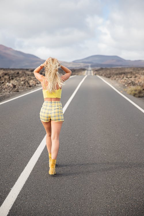 Woman in Blue and White Plaid Skirt Walking on the Road