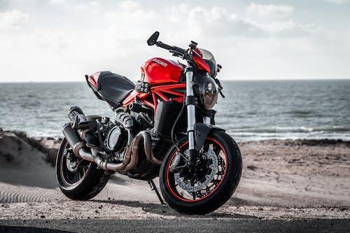 Red and Black Sports Bike on Brown Sand Near Sea