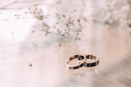 Two Silver-colored Rings on Beige Surface