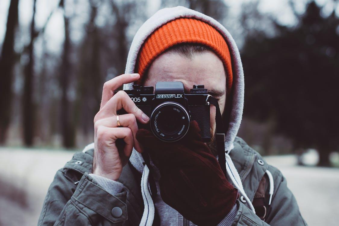 Man Wearing Gray Hooded Jacket Holding Black Camera