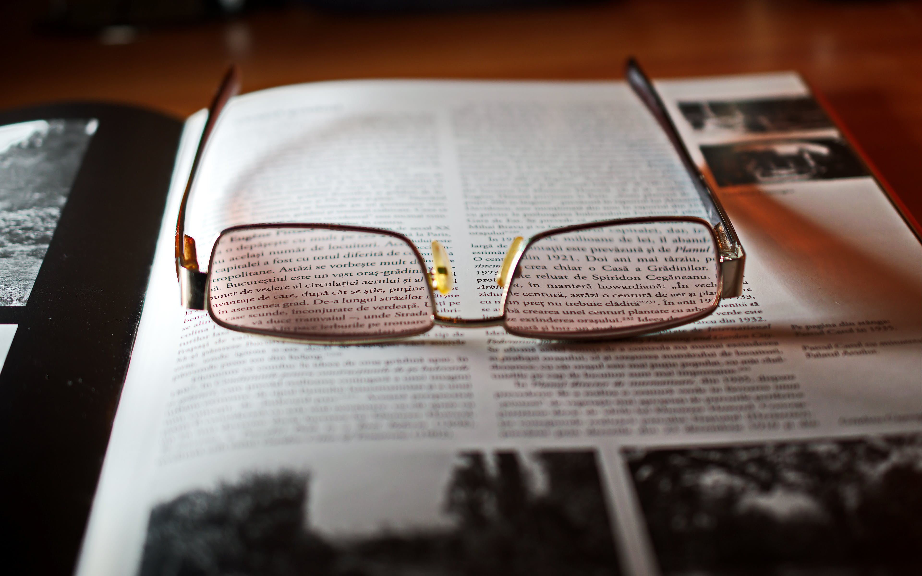 Eyeglasses With Gold-colored Frame on Opened Book