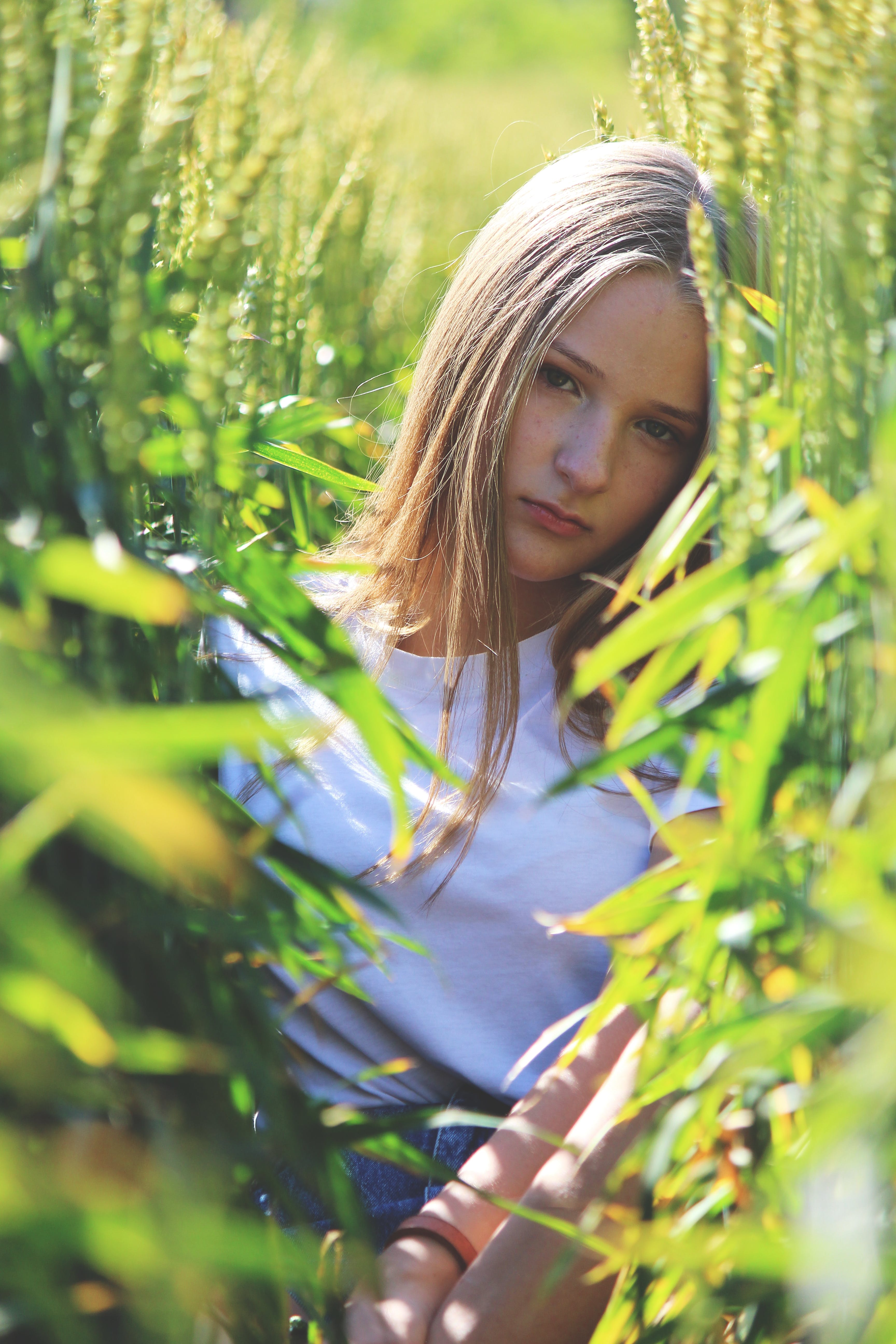 Selective Focus Photo of Woman Wearing White Shirt Between Green Wheat