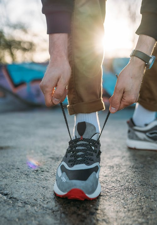 Close-Up Shot of a Person Tying Shoes