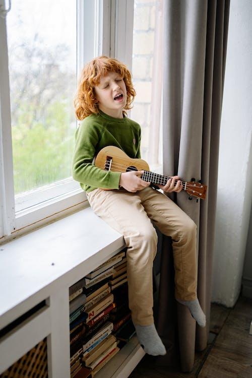 A Redheaded Boy Playing Ukulele while Sitting