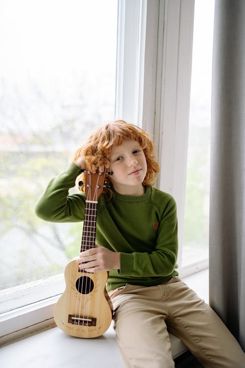 A Redheaded Boy Holding a Ukulele while Looking at Camera
