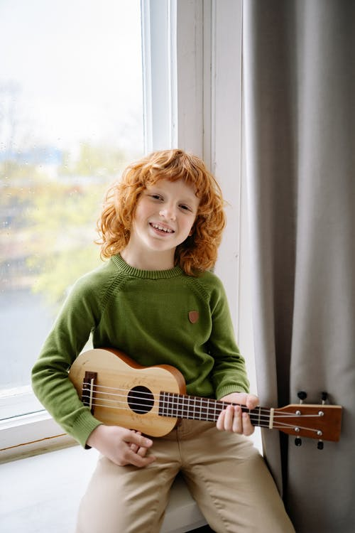 A Happy Redheaded Boy Holding a Ukulele while Looking at Camera