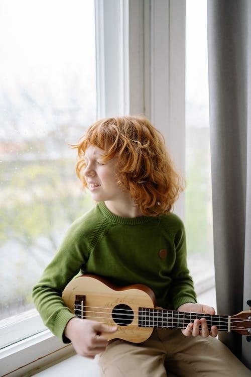 A Redheaded Boy Playing a Ukulele while Sitting