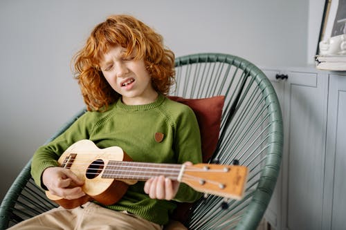 A Redheaded Boy Playing Ukulele while Sitting on a Chair