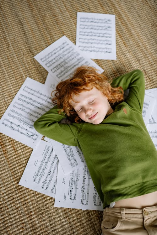 A Boy Lying Down on Musical Notation Papers