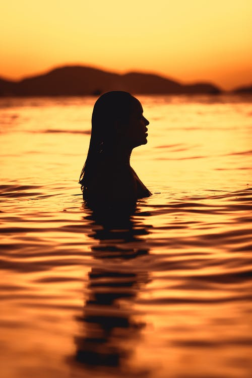 Silhouette of Woman in Water during Sunset