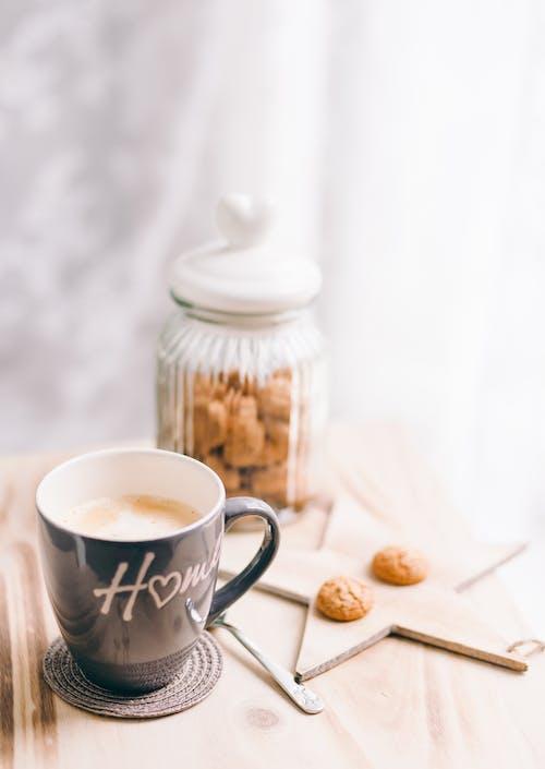 White and Black Ceramic Mug Beside White Ceramic Teapot on Brown Wooden Table