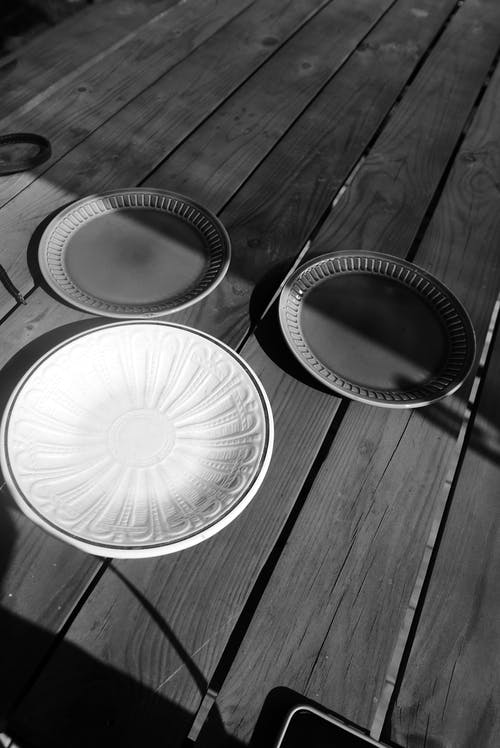 A Grayscale of Plates on a Wooden Table