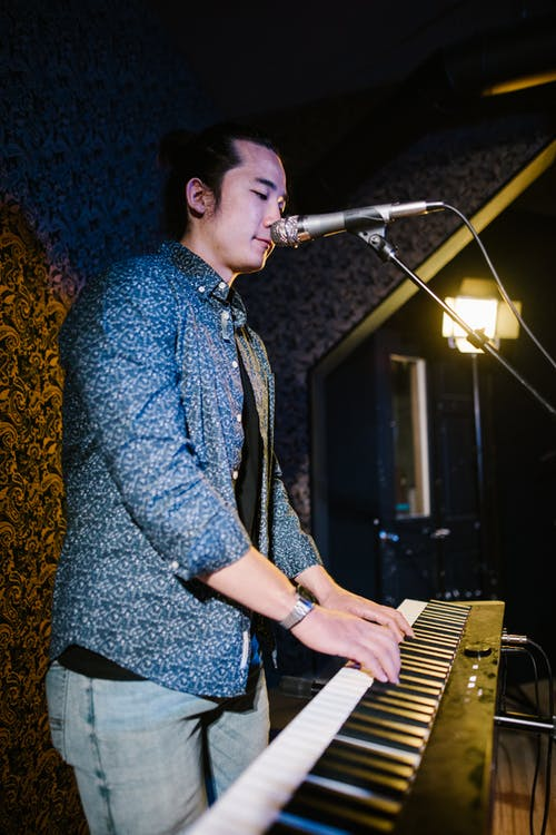 A Man in Button-Up Shirt Playing Piano